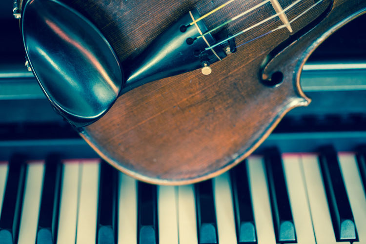 Close-up of violin on piano keys