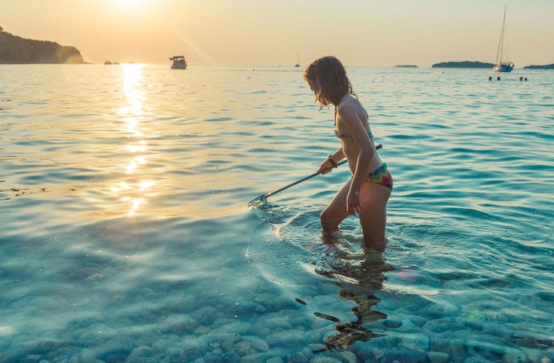 Girl standing in sea water at shore during sunset