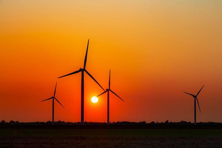 Silhouette wind turbines on field against orange sky