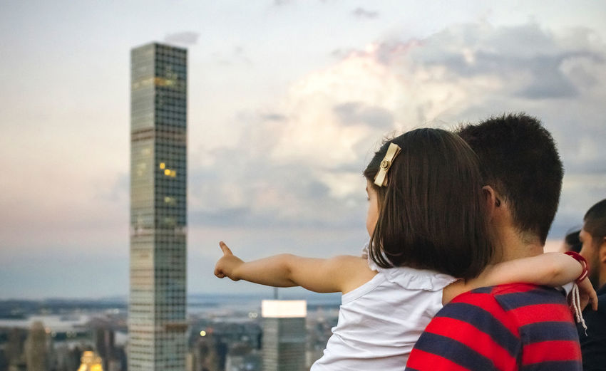 Father with daughter against sky in city