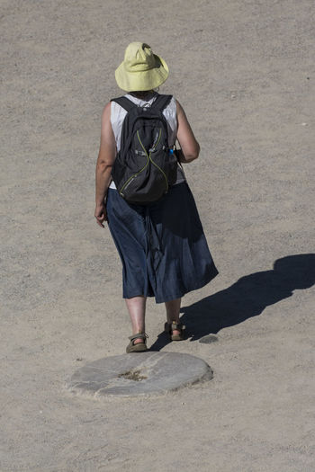 Rear view of woman standing on footpath