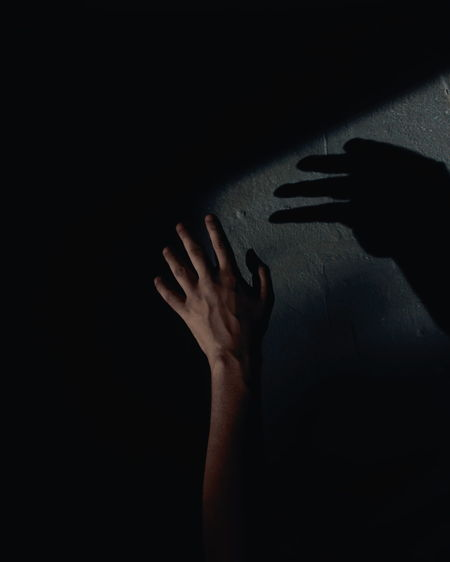Close-up of hand touching shadow on wall in darkroom