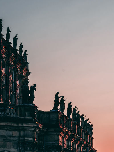 Low Angle View Of Silhouette Statues Against Sky During Sunset