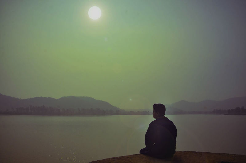 Rear view of man sitting by lake against sky