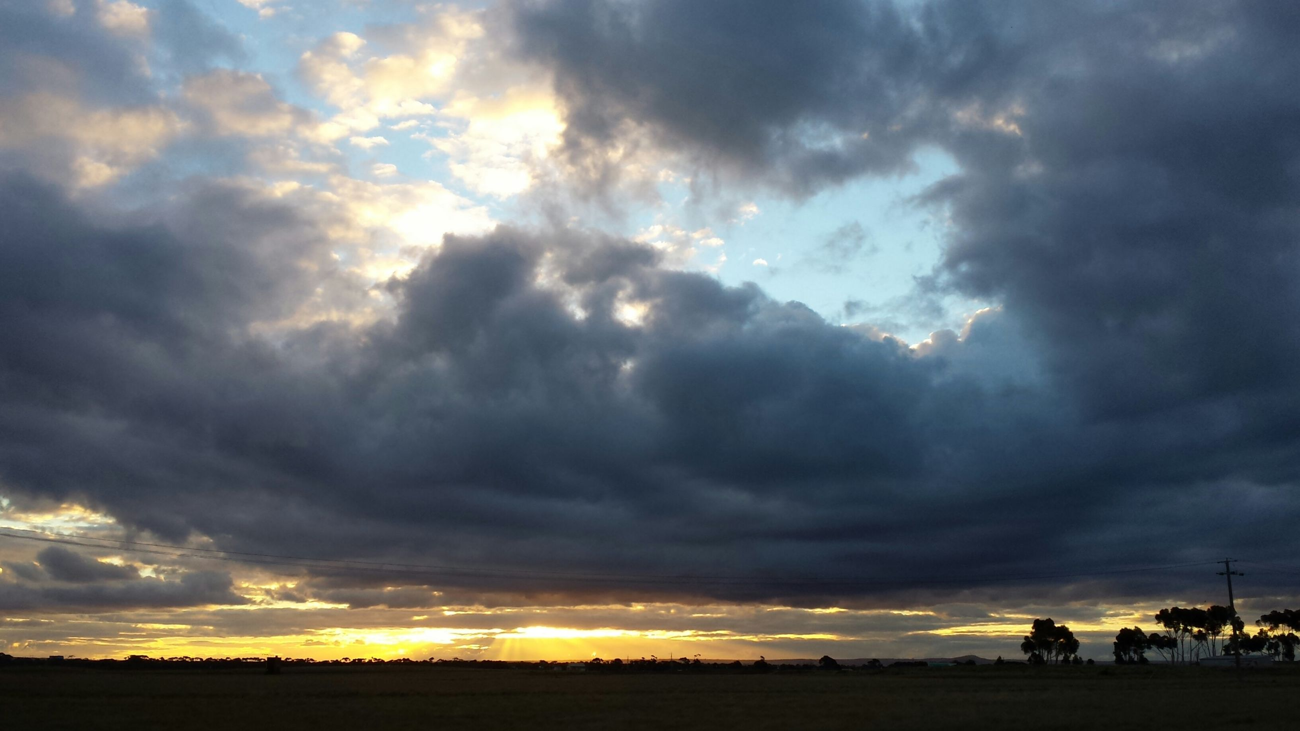 sky, sunset, cloud - sky, cloudy, scenics, tranquil scene, beauty in nature, dramatic sky, landscape, tranquility, silhouette, cloud, overcast, weather, nature, cloudscape, moody sky, idyllic, field, atmospheric mood