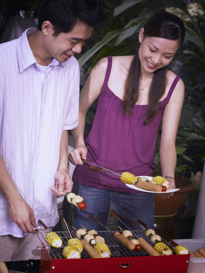 Young couple preparing food on barbecue grill against swimming pool