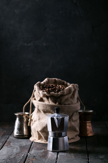 Roasted Coffee Beans In Sack By Espresso Maker Against Wall