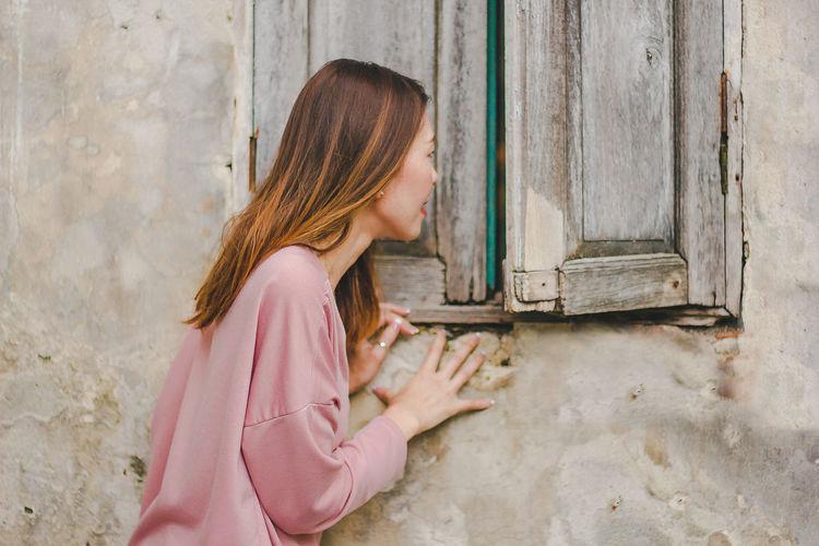 Side view of mid adult woman peeking through wooden window