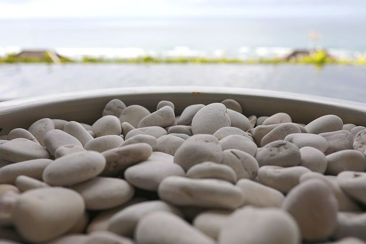 Close-up of pebbles in container against sea