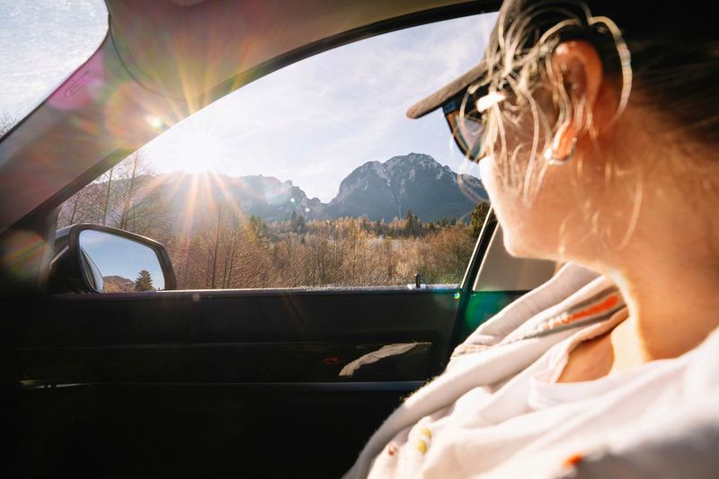Portrait of woman in car during winter with sunbeam