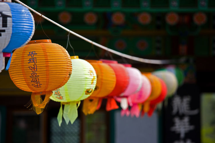 Close-up of multi colored lanterns hanging in row