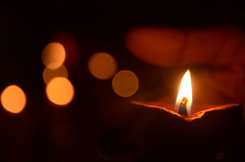 Close-Up Of Hand Holding Diya At Night