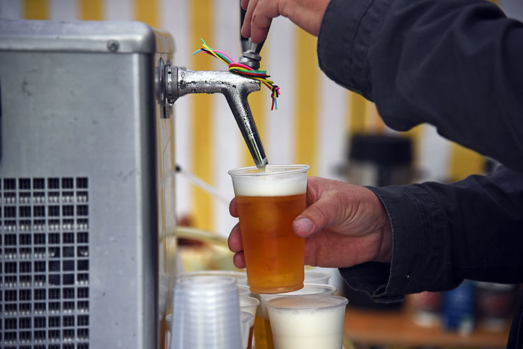 Cropped hands of man filling beer in glass