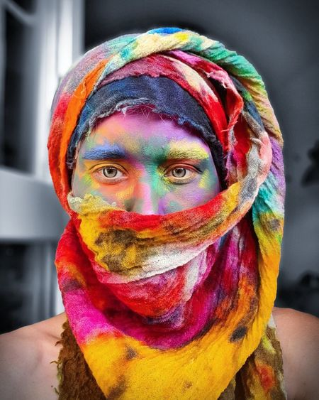 Portrait of man with multi colored face