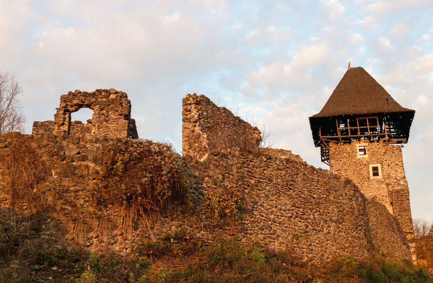 The last rays of the sun illuminate the ruins of the old castle. Nevytsky Castle near Uzhgorod, Ukraine Ancient Ancient Ruins Architecture Castle Castle Ruin Castle Tower Castle View  Castle Walls Cloud - Sky History Low Angle View No People Old Castle Old Castle Walls Outdoors Setting Sun Sky Walls