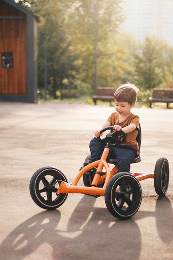 Full length of boy sitting at toy car
