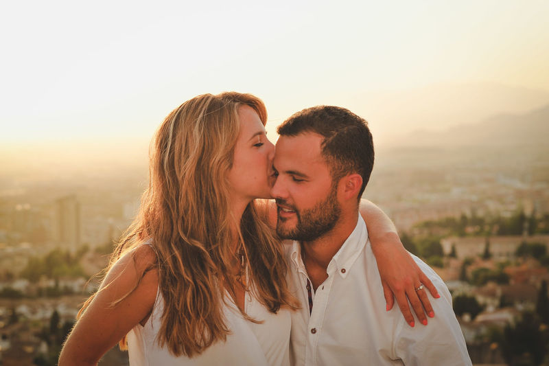 Close-Up Of Young Woman Kissing Man Against City During Sunset