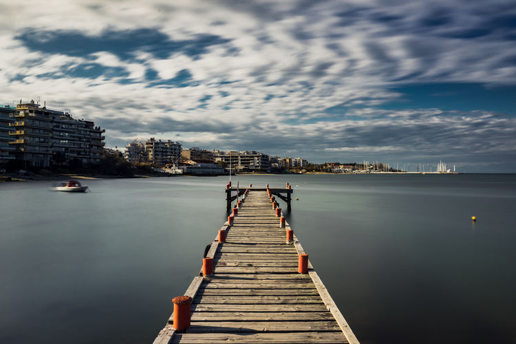 Pier over sea against cloudy sky in city