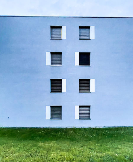 Building on field against sky