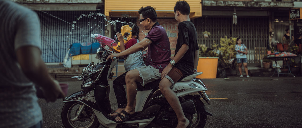 Songkran Festival Thailand Adult Architecture Bicycle Casual Clothing City Communication Group Of People Land Vehicle Leisure Activity Lifestyles Mask Men Mode Of Transportation Motorcycle People Real People Street Transportation Young Adult Young Men