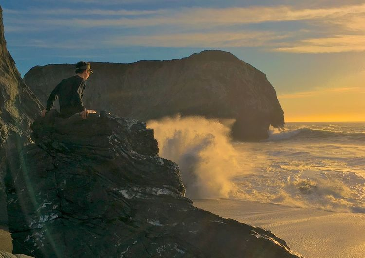 Man sitting on rock formation at beach during sunset