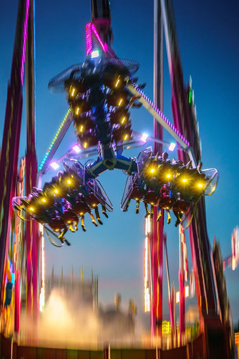 Low angle view of illuminated amusement park ride against sky at night