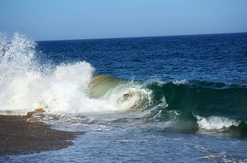 View of waves against clear blue sky