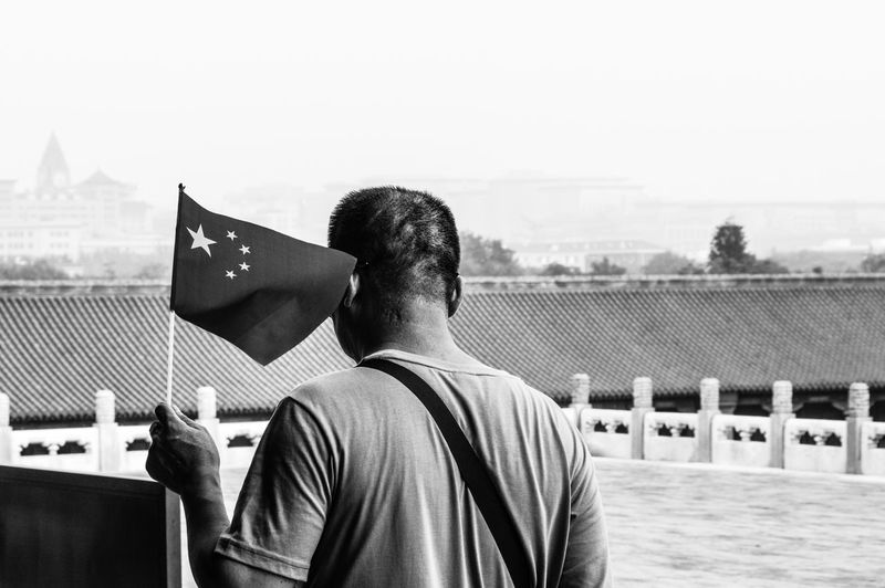 Rear View Of Man Holding Chinese Flag At Forbidden City