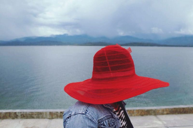 Woman in red hat against calm lake