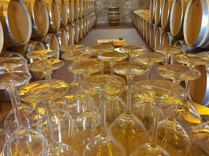 Upside down wineglasses on table against barrels in cellar