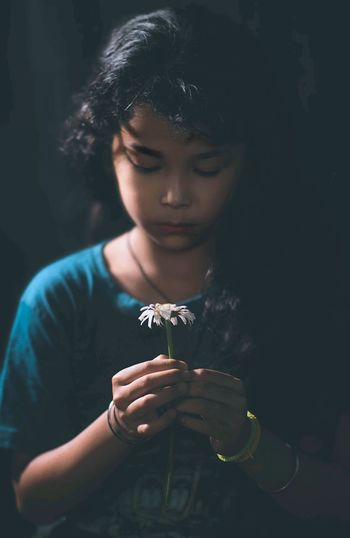 Close-up of cute girl holding flower