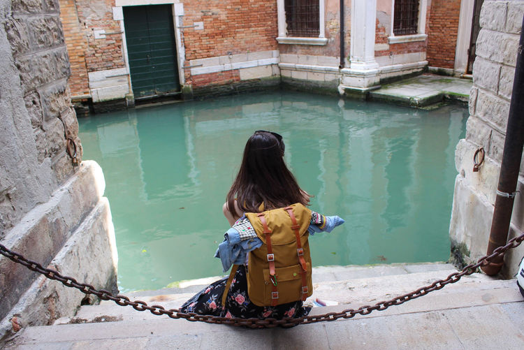 Rear view of woman sitting in canal