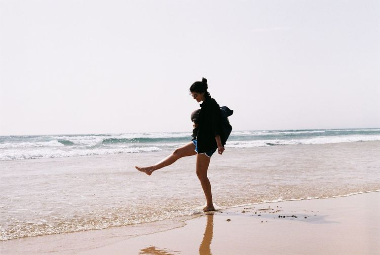 Full length of woman splashing water while standing on shore at beach against clear sky