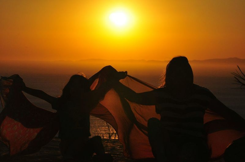 Mother And Daughter Holding Fabric Against Sea During Sunset