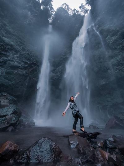 Women standing on rock against waterfall