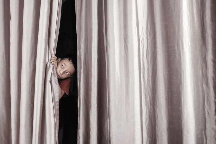 Portrait of young woman hiding behind curtain at home