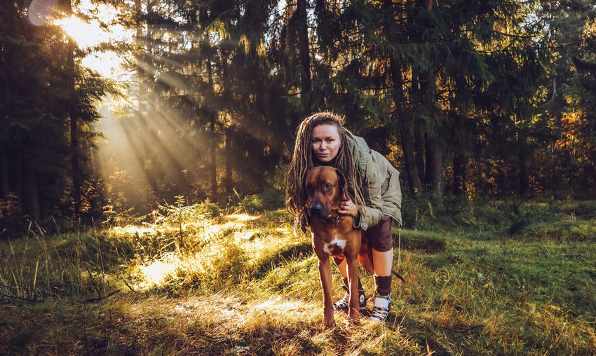 Young smiling woman with dreadlocks in autumn fall forest in the morning sunshine playing with a dog ridgeback Tree Plant Looking At Camera Portrait Land One Person Real People One Animal Pets Mammal Young Adult Leisure Activity Domestic Front View Domestic Animals Animal Themes Lifestyles Nature Animal Dog Hair Hairstyle Pet Owner Outdoors Beautiful Woman Dreadlocks Ridgeback