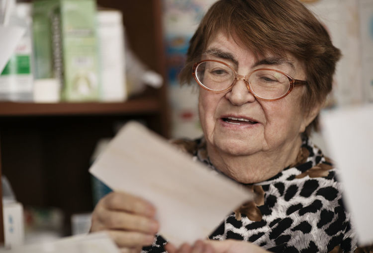 Close-up of senior woman reading paper while sitting at home