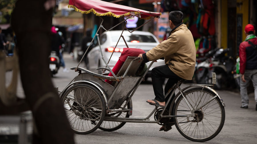 Rear view of people riding bicycle on street