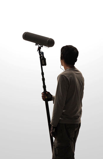 Boom Microphone hold up high by video or film production crew team man and recording sound for movie in a big studio. One Person Three Quarter Length Men Real People Holding Rear View Standing Lifestyles Casual Clothing Leisure Activity Tripod White Background Technology Sky Nature Copy Space Occupation Photography Themes Young Men Photographer Boom Microphone Hold Up High By Video Or Film Production Crew Team Man And Recording Sound For Movie In A Big Studio. Boom; Microphone; Mic; White; Sound; Film; Background; Equipment; Audio; Windshield; Head; Recording; Headphones; Holding; Filming; Media; Crew; Guy; Camera; Pole; Set; Studio; Movie; Real; Production; Technology; Isolated; Broadcast; Up; Shoot; Hold; Hig