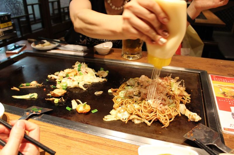 Midsection of woman pouring mayonnaise on noodles at restaurant