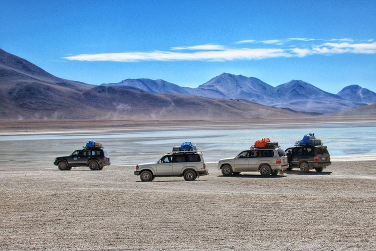 Scenic view of 4-wheel cars parked in the desert against sky