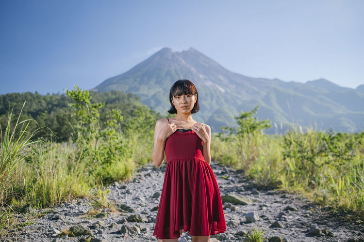 Portrait of woman standing on rocks against mountain