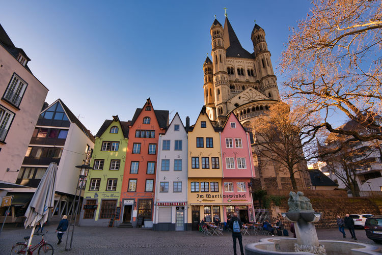 Cologne, GERMANY - February 15, 2019: Many unidentified individuals enjoy the warm sundown in the historic old town Building Exterior Architecture Built Structure Building Sky City Nature Tree Day Street Clear Sky Religion Belief Place Of Worship Incidental People Bare Tree Spirituality Residential District Travel Destinations Outdoors Row House