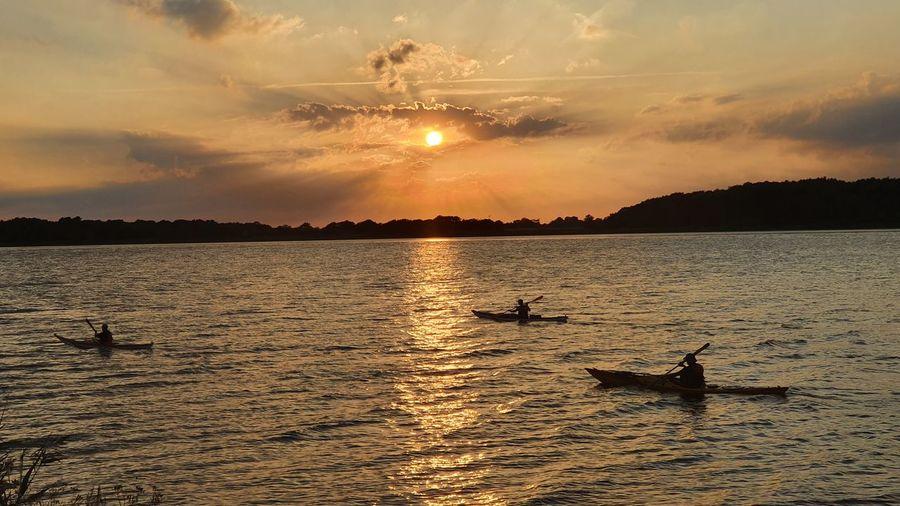 Silhouette ducks swimming in sea against sunset sky