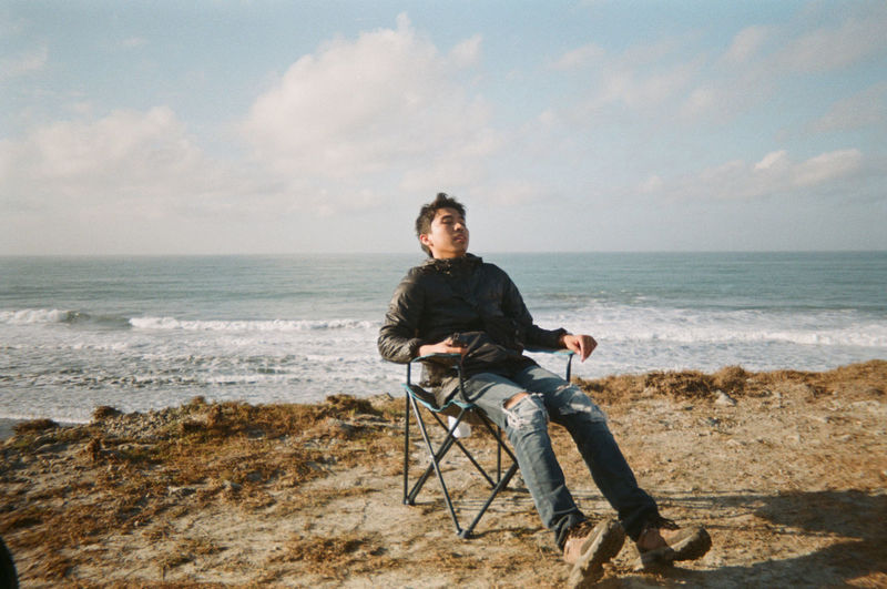 Man sitting on shore at beach against sky