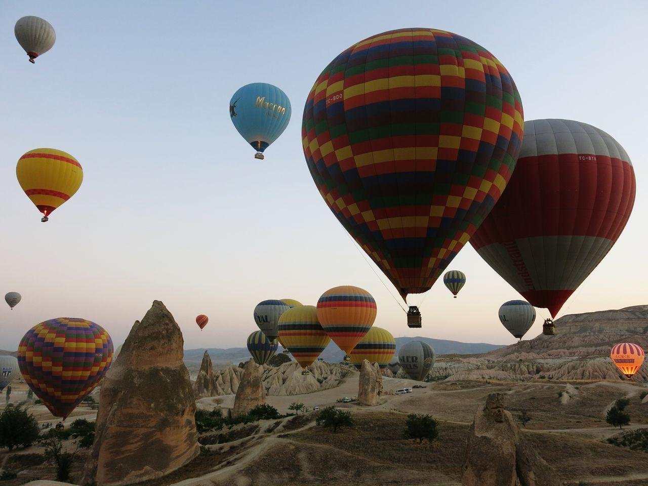 Hot air balloons flying over cappadocia against sky
