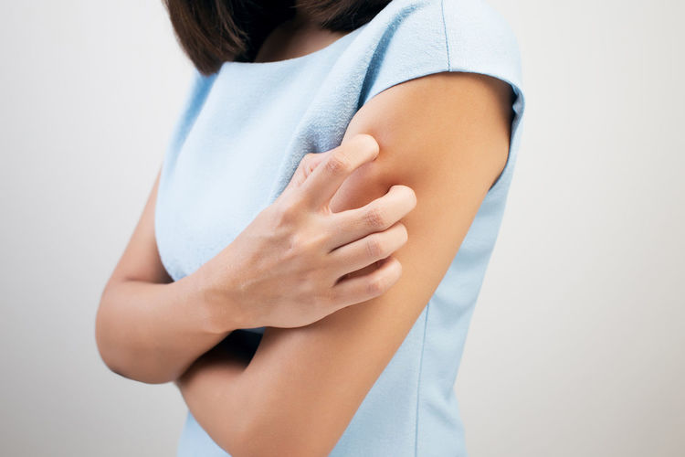 Midsection of woman scratching arm against white background