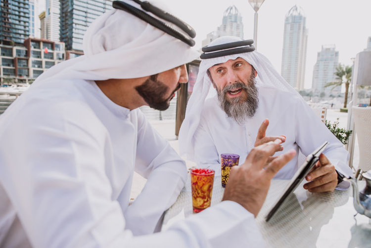 Men wearing dish dash discussing over digital tablet outdoors in city
