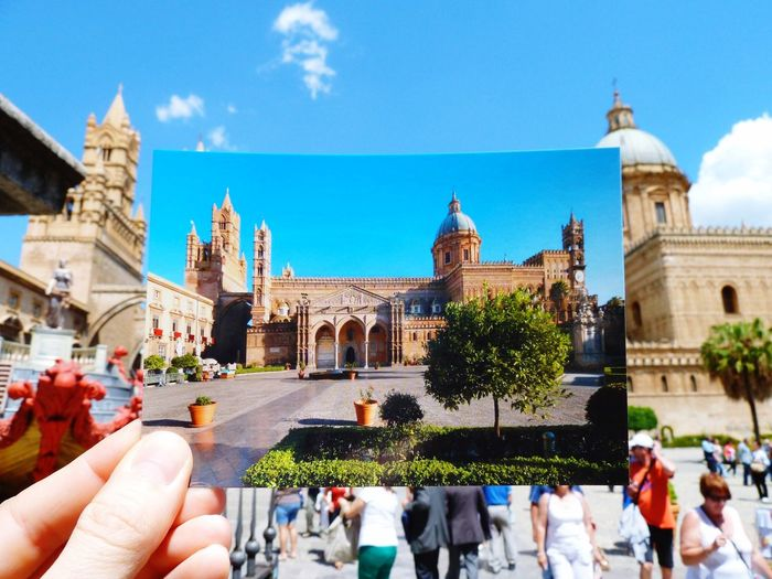 Cropped image of hand holding photograph against palermo cathedral